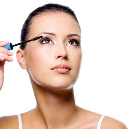 Beautiful woman applying mascara on her eyelashes - isolated on white Stock Photo - 8040934
