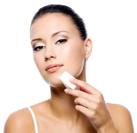 Beautiful young woman applying foundation on face with sponge on white background photo