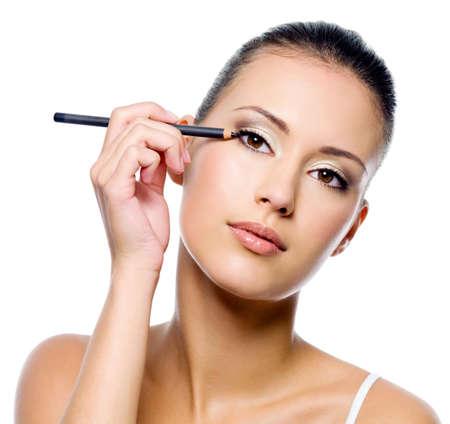 maquillage yeux: Jeune femme belle application eye-liner sur la paupi�re au crayon - isol�  Banque d'images