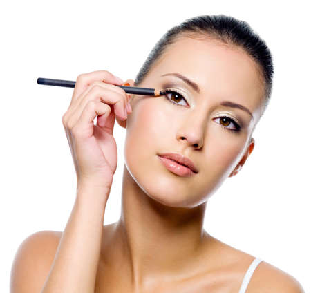 black makeup: Young beautiful woman applying eyeliner on eyelid with pencil - isolated