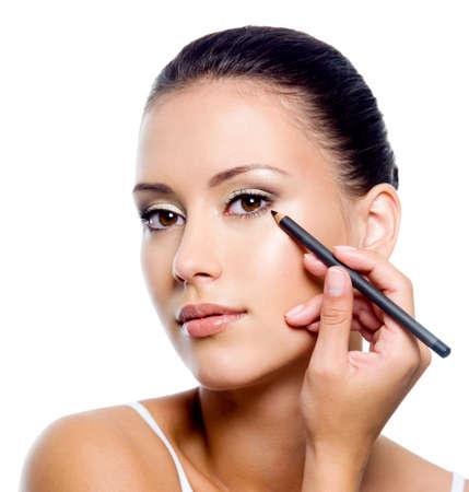 eyeliner: Young beautiful woman applying eyeliner on eyelid with pencil - isolated