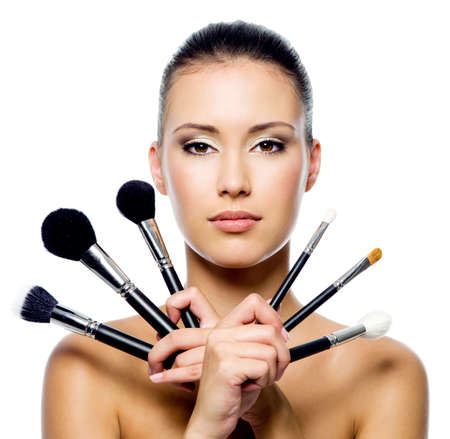 Beautiful woman with makeup brushes near her face - isolated on white Stock Photo - 8041197