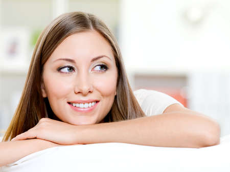 Beautiful smiling womans face looking away - indoors photo