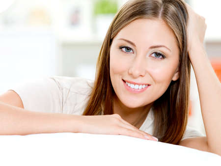 sits: Happy beautiful woman sits on a sofa at home Stock Photo
