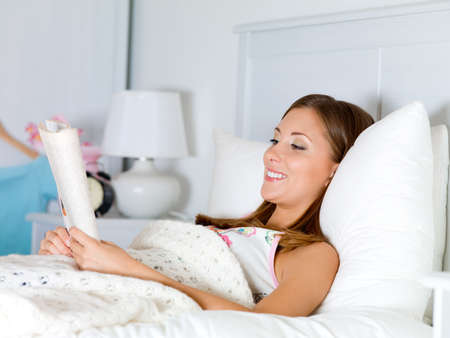 beautiful happy woman reads the book has a rest on a bed photo