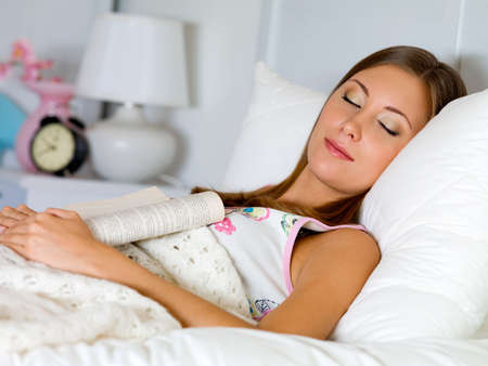 beautiful woman sleeps with the book at night in the bed photo