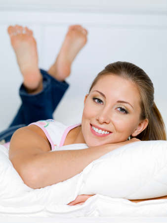 portrait of happy woman lies on a pillow on the bed Stock Photo - 8040964