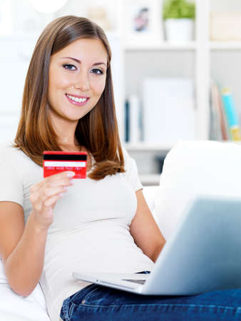 Portrait of happy young beautiful woman holding credit card and using laptop Stock Photo