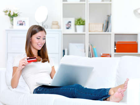 young beautiful woman holding credit card and  looks in the laptop - indoors photo