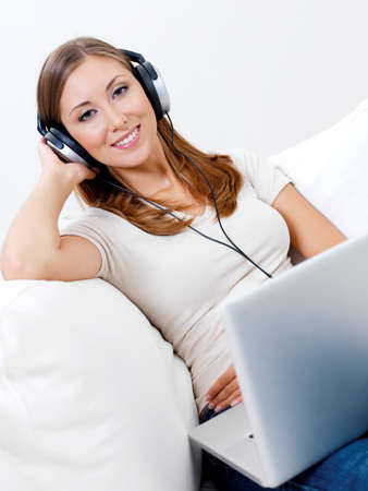 Portrait happy young woman listening music in headphone from laptop at home photo