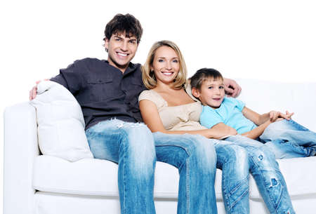 Happy young family with child siting on white sofa isolated Stock Photo - 8078209