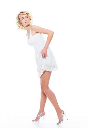 Beautiful sexy woman with modern white dress posing in studio looking away photo