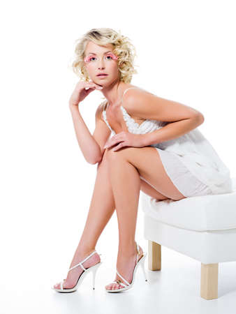 Beauty sexy woman with beautiful legs sits on white chair photo
