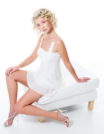 beautiful woman with sexy  legs sits on white chair - high angle photo