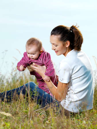 Happy youngl mather with beby outdoor siting on grass photo