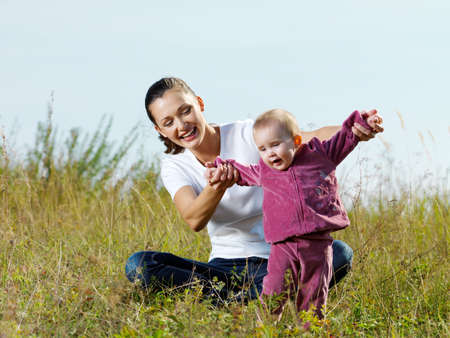 Happy young beautiful mather with smiling beby on nature outdoor photo