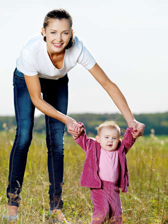 Happy young beautiful mather with smiling beby on nature photo