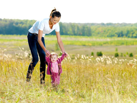 Happy young beautiful mather with smiling beby on nature
