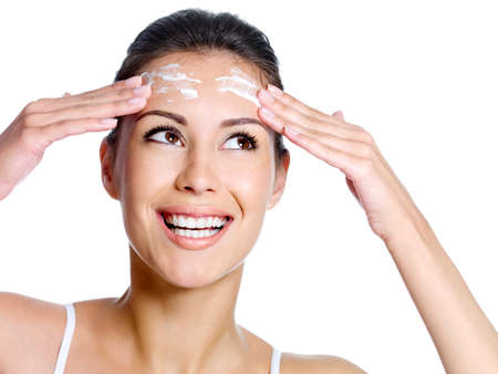Beautiful happy smiling woman with cream on the forehead of her face looking up - isolated Stock Photo - 8078579