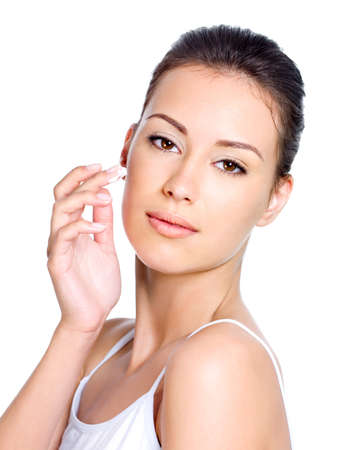 Beautiful woman with easy smile applying moisturizer facial cream - isolated  photo