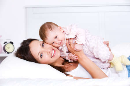 bonding: Portrait of happy young mother lying with her baby on the bed at home Stock Photo