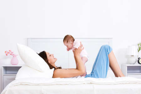 Young mother playing with her little baby on the bed - indoors photo