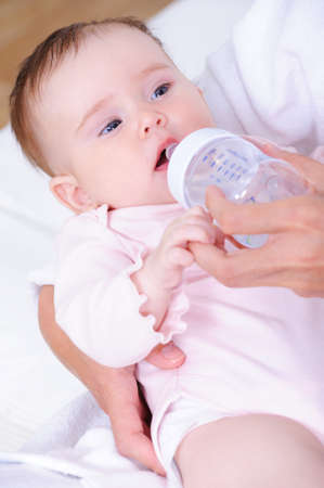 Beautiful pretty little baby with plastic bottle of daily food - close-up photo