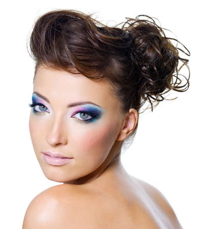 Beautiful and sexy woman face with multi colored make-up and creative hairstyle photo