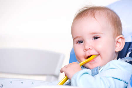 Beautiful happy toddler with spoon sitting on chair Stock Photo - 8197210