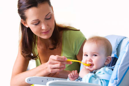 Mother feeding hungry baby in the highchair indoors  Stock Photo - 8197453