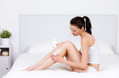 Beautiful young woman caring about her legs with moisturizing lotion - indoors photo