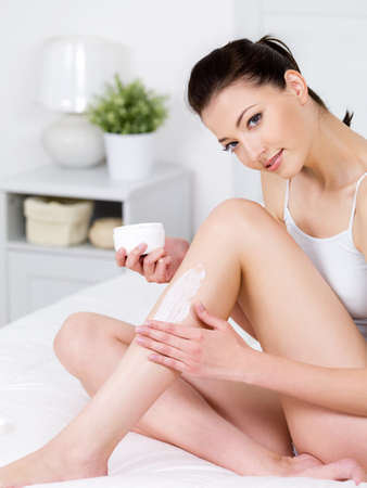 Beautiful young smiling woman sitting on a bed and applying cream on her attractive legs - vertical photo