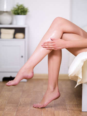 Beautiful fresh legs of young woman applying cream on it - indoors photo