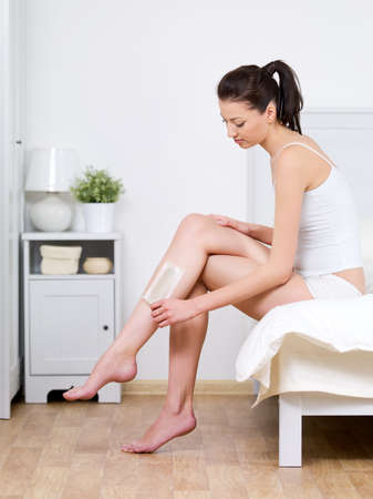 Beautiful young woman depilating her attractive legs by waxing at home - indoors photo