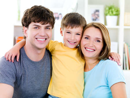 Close-up portrait of happy faces of smiling friendly young famile with son Imagens