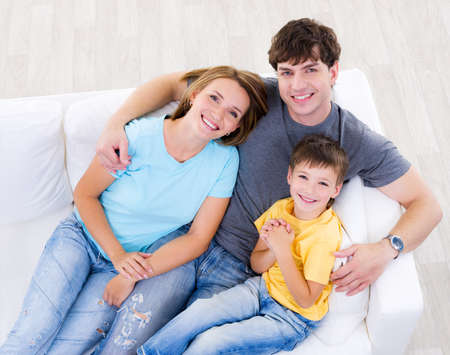 casuals: Portrait of happy laughing young family with son in casuals on the sofa at home - high angle Stock Photo