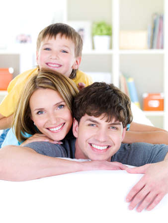 Close-up happy smiling faces of young family of three people with son - indoors photo