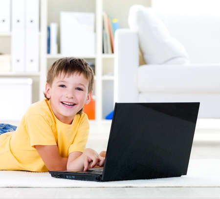 kids room: Laptop for happy little boy lying on the floor at home - indoors