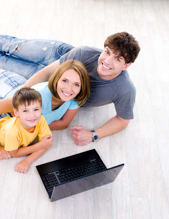 High-angle portrait of happy laughing young family with son lying on the floor with laptop photo