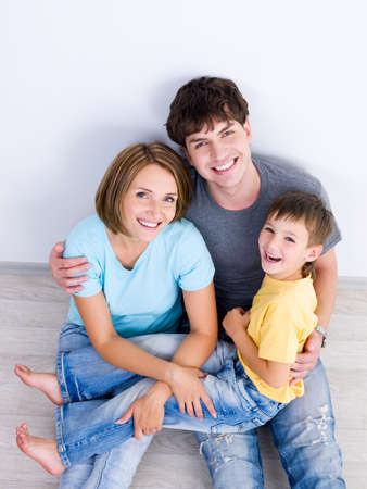 Happy laughing family with young boy sitting on the floor in casuals - high-angle photo