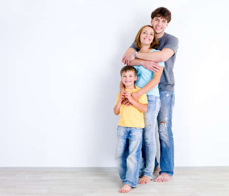 family  room: Happy family of three people standing in embrace near the empty wall Stock Photo