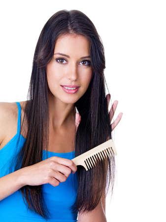 Retrato de la joven y bella mujer peinándose su cabello largo - aislado en blanco