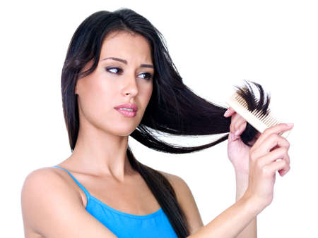 ends: Young beautiful woman combing hair and looking on the ends of hair - isolated