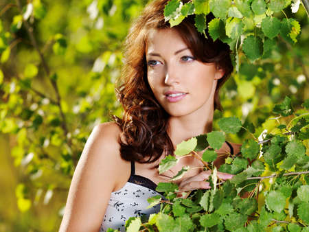 Beautiful face of the young sexy woman posing near the green tree on nature Stock Photo - 8197135