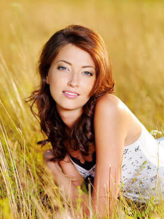 Beautiful face of the young sexy woman posing lying on the grass photo