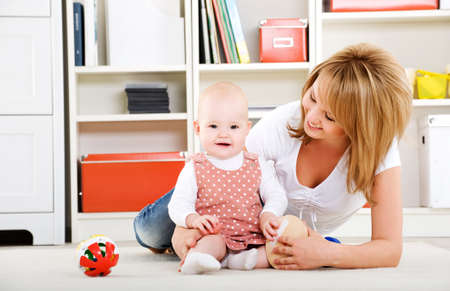 01: Beautiful baby playing with toys with happy mother  indoors Stock Photo