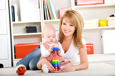 Beautiful baby playing with toys with happy mother  indoors photo