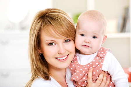 Beautiful happy mother holding  newborn baby on hands - Indoors photo