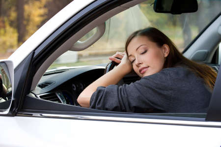 weariness: beautiful young  woman sleeps in the car  - outdoors Stock Photo
