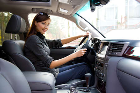 look inside: beautiful young happy woman posing inside of  the new car